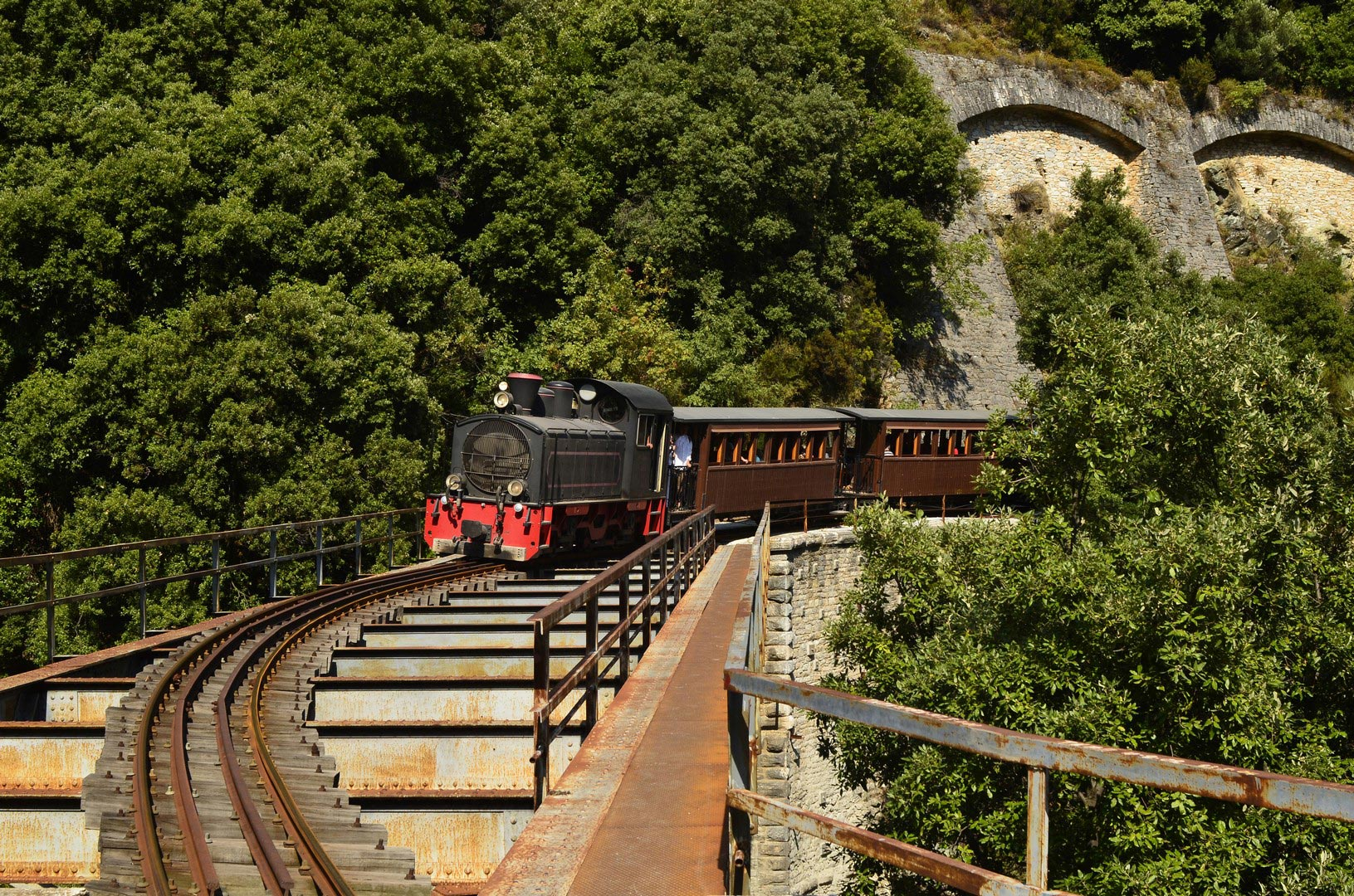 Greece,-the-Montzouris-Smudgy-train---Pelion-train---crossing-a-bridge---shutterstock_87084818