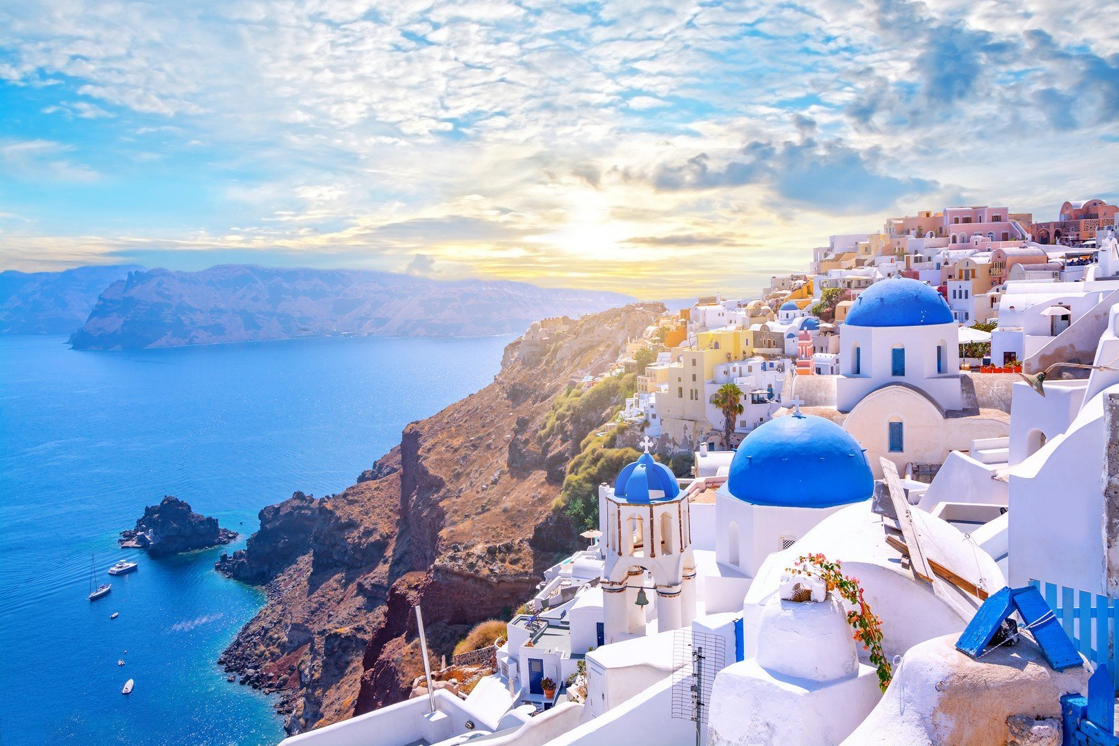 Beautiful Oia town on Santorini island, Greece. Traditional white architecture and greek orthodox churches with blue domes over the Caldera, Aegean sea shutterstock_1345474721