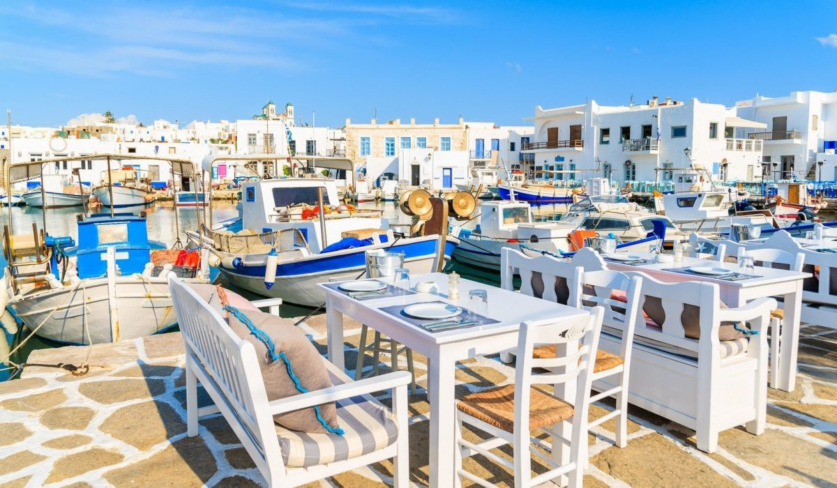 Greek taverna tables and fishing boats anchoring in Naoussa port, Paros island, Greece shutterstock_524187643