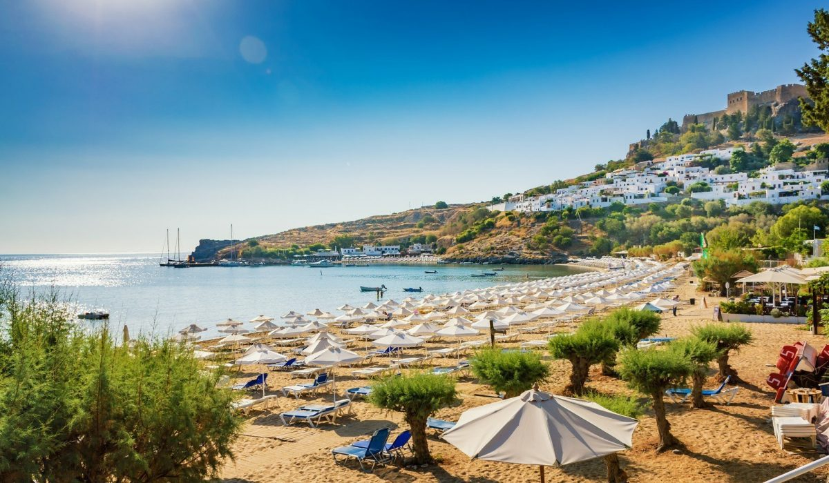 View of sandy beach in Bay of Lindos, Acropolis in background (Rhodes, Greece) shutterstock_783410419